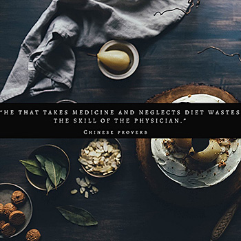 """This is a top-down image of a dark blue painted table with a pear, slivered nuts and some herbs, there's a medium blue napkin. There's text overlay that says """"He That Takes Medicine and neglects Diet Wastes the Skill of the Physician"""" ~ Chinese Proverb"""
