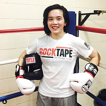 """This is an image of Dr. Khanita posing in a boxing ring in a white t-shirt and grey shorts. The t-shirt says """"RockTape: Go stronger, longer"""" She is wearing white padded boxing gloves and is holding a black padded boxing helmet with the word Title across it. It appears as though she just finished sparring."""