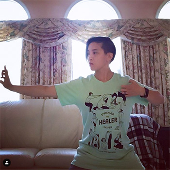 """This is an image of Dr. Khanita practicing kung fu in a living room. She's wearing a light green t-shirt that says """"Empower the HEALER within"""""""