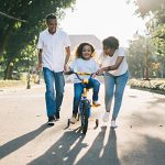 This is an image of a dad and mom helping their daughter learn to ride on a bike with training wheels.
